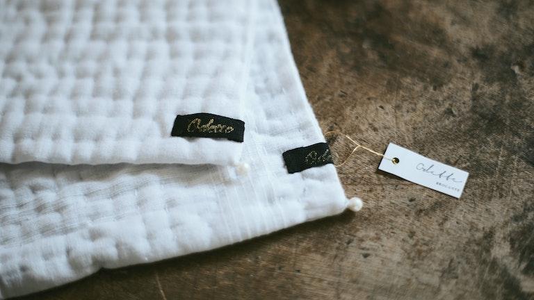 シンプルな白の布地に、「Odette」のオリジナルタグやパールのビーズがさりげないかわいさを添える