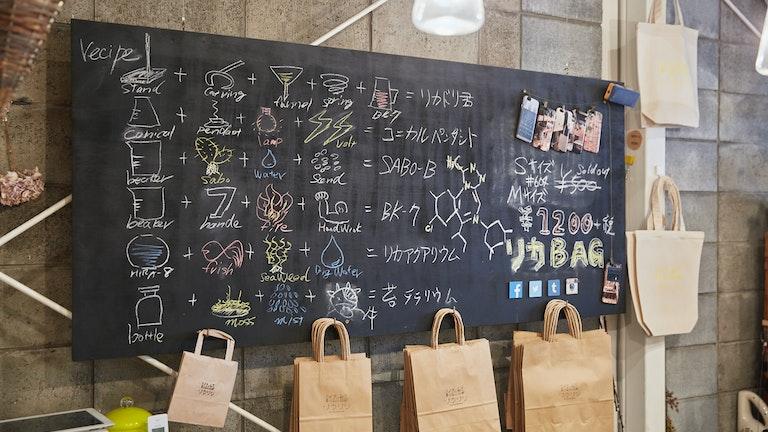 レジカウンター奥の黒板には、「リカアクアリウム」や「苔テラリウム」など理化学ガラスを使ったレシピが