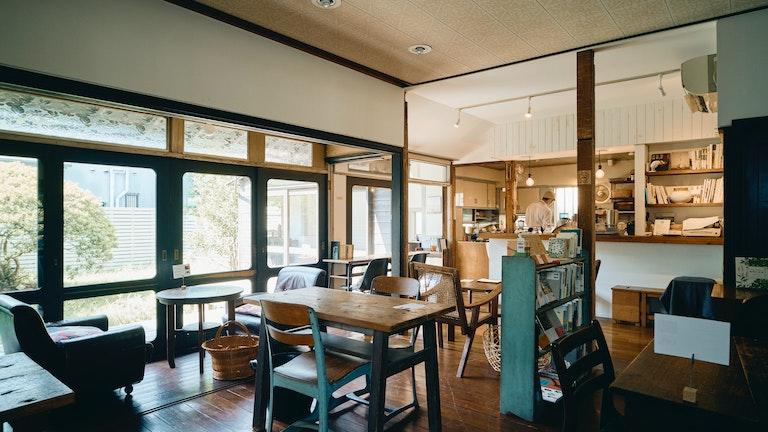 大きな窓から陽の光が差し込む、あたたかみのあるカフェスペース