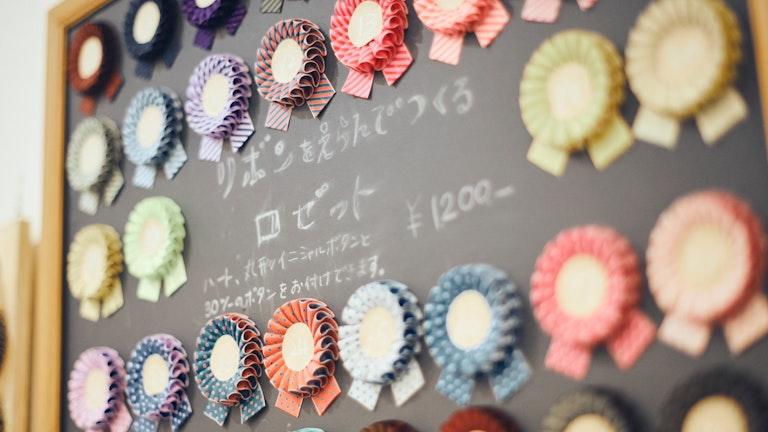 ハート型やイニシャルの刺繍されたボタンと好きなリボンを組み合わせてつくるロゼット(¥1,200)