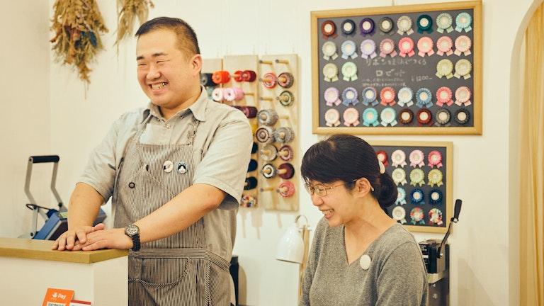 店主の片岡さんご夫妻。刺繍のイラストは、ご主人自らひとつひとつデザインしている