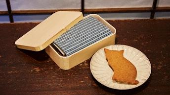 包み紙はブックカバーにもなるという嬉しい心遣い。猫形のジンジャークッキー〔みかもとわっぱ(¥1,500/税抜)〕