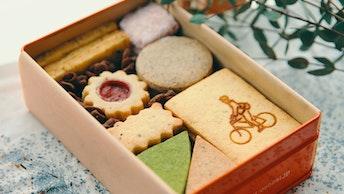 パズルの様に美しく並んだ9種のクッキー。様々な味わいを楽しめる〔オリジナルクッキー缶(¥2,500/税抜)〕