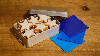 シルバーの缶もシンプルでおしゃれ。付属の折り紙に乗せれば夜空が完成!〔夜空缶(¥1,500/税抜)〕