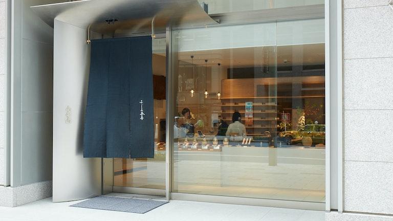 中央通りに面する、ガラス張りのモダンな店構え。濃紺の暖簾が山本山の伝統を感じさせる