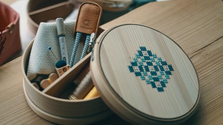 蓋が刺繍枠になっている曲げわっぱの道具箱(¥12,000/税抜)。結婚祝いとしても人気
